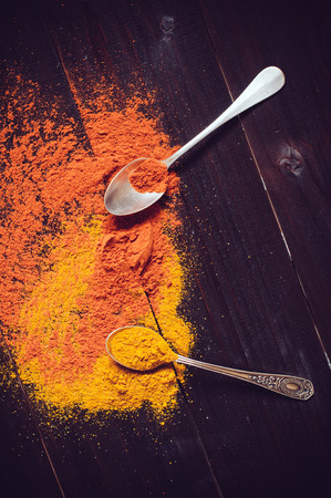 curry powder: Bright spices and spilled curry powder, paprika and spoon fell on the wooden board