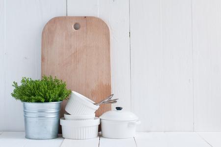 Cottage Leben, Land Küche Dekoration: eine Zimmerpflanze in einem Metalltopf, Küche Geschirr, Besteck und Servietten auf weiß lackiert Bord. Gemütliches Haus Landleben Hintergrund.