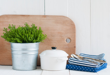 country kitchen: Cottage life, country kitchen decoration: a house plant in a metal pot, kitchen pottery, utensils and napkins on white painted board. Cozy home country life background is. Stock Photo