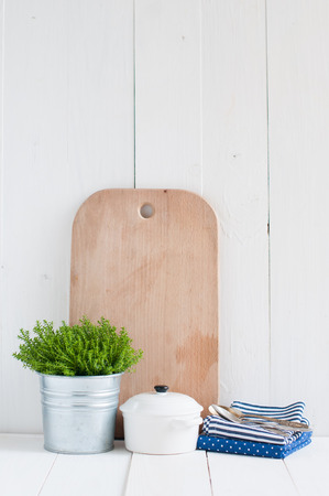 Cottage life, country kitchen decoration: a house plant in a metal pot, kitchen pottery, utensils and napkins on white painted board. Cozy home country life background is. photo
