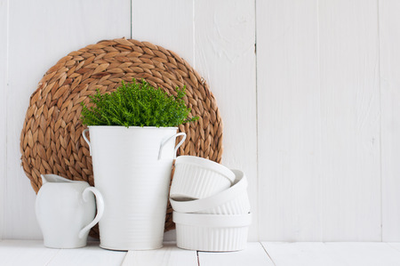 Cottage life, country kitchen decoration: a house plant in a metal pot, kitchen pottery, utensils and napkins on white painted board. Cozy home country life background is. Stock Photo