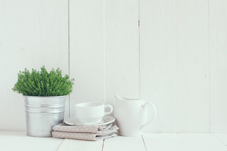 Cottage life, country kitchen decoration: a house plant in a metal pot, kitchen pottery, utensils and napkins on white painted board. Cozy home country life background is. 免版税图像