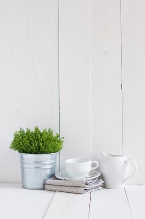 코티지 생활, 국가 부엌 장식 : 금속 냄비, 주방 도자기, 흰색 페인트 보드의기구와 냅킨의 집 식물. 아늑한 집 시골 생활의 배경입니다.