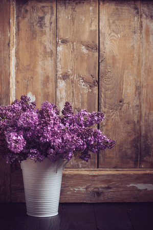 Bouquet of lilac flowers in a pot on a background of vintage wooden board, home decor in a rustic style