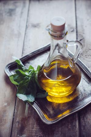 aceite de cocina: Aceite de oliva fresco en una botella de la vendimia y el manojo de albahaca verde sobre una bandeja de metal sobre una tabla de madera