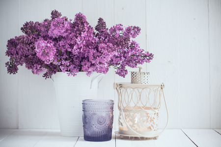 blue white kitchen: Bouquet of lilac flowers in vintage vase and decorative candlestick on a white wooden board, wedding decoration in a rustic style
