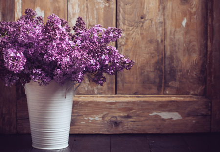 Bouquet of lilac flowers in a pot on a background of vintage wooden board, home decor in a rustic style photo