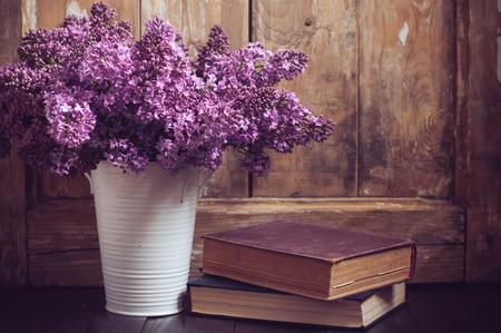 Bouquet de fleurs de lilas dans un pot et de vieux livres sur un fond de carte en bois d'époque, décor à la maison dans un style rustique
