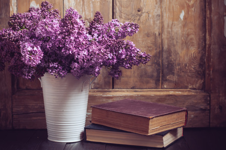 Bouquet of lilac flowers in a pot and old books on a background of vintage wooden board, home decor in a rustic style
