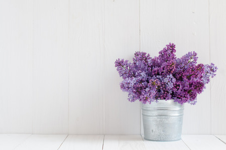 Bouquet of beautiful spring flowers of lilac in a vase on a white vintage wooden board, home decor in a rustic style photo