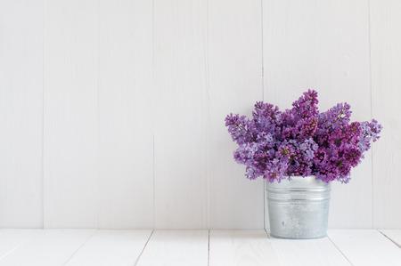 Boeket van prachtige lente bloemen van lila in een vaas op een witte vintage houten plank, woondecoratie in een rustieke stijl Stockfoto