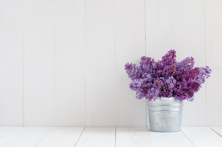 colores pastel: Ramo de hermosas flores de primavera de color lila en un florero en una tabla de madera de la vendimia blanco, decoraci�n para el hogar en un estilo r�stico
