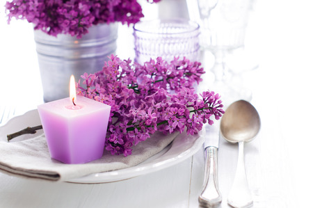 Festive wedding table setting with lilac flowers, candles, vintage cutlery, glasses and dishes Zdjęcie Seryjne