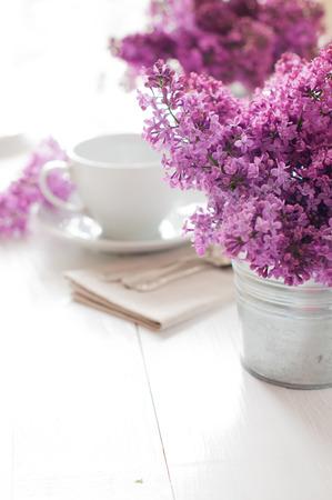 arreglo floral: T� de la ma�ana ajuste de la tabla delicado con flores de color lila, cucharas y utensilios de �poca sobre una tabla de madera blanca