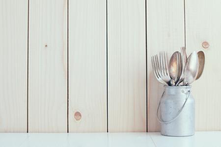 Home Kitchen Decor: vintage bestek, lepels en vorken in zink kan op een houten plank achtergrond, gezellig arrangement retro-stijl, zachte pastelkleuren. Stockfoto
