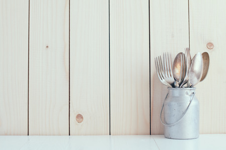 Home Kitchen Decor: vintage cutlery, spoons and forks in zinc can on a wooden board background , cozy arrangement retro style, soft pastel colors.