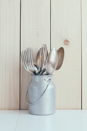Home Kitchen Decor: vintage cutlery, spoons and forks in zinc can on a wooden board background , cozy arrangement retro style, soft pastel colors. photo