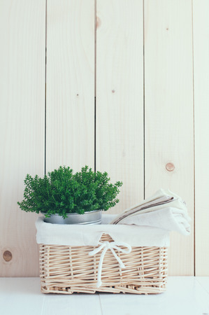 country kitchen: Home decor: vintage wicker basket, house plant and a stack of linen napkins on a wooden board  background, cozy composition retro style, soft pastel colors.