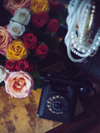 Old vintage black rotary phone and a bouquet of fresh roses on an old dresser in interior, retro style home decor photo