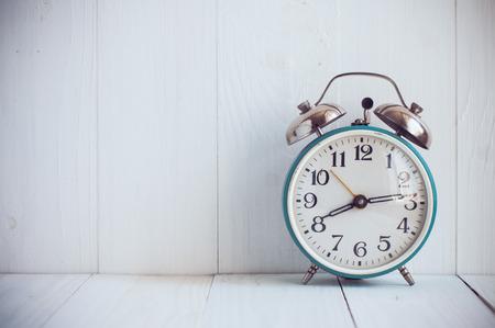 Big old vintage alarm clock with bells, painted white wooden background Stock Photo