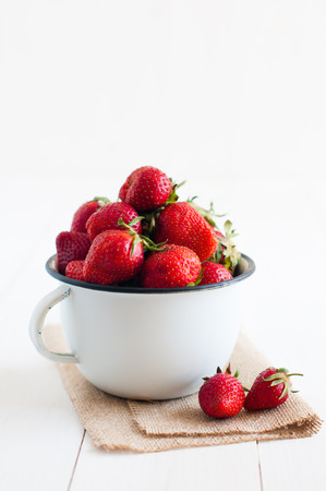 Fresh ripe red strawberries in white enamel mug and rough cloth on a table, natural food background photo