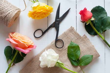shear: Floral arrangement, vintage floristic background, colorful roses, antique scissors and a rope on white painted wooden table