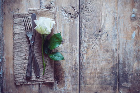 Vintage cutlery, antique silverware, fork, knife and a rose flower with rough cloth on an old wooden background photo