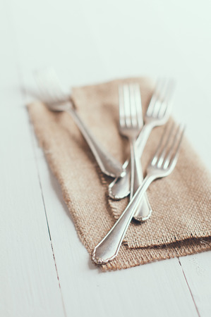 Vintage cutlery, antique silverware, four forks with rough brown cloth on an white painted wooden background photo