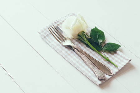 Vintage cutlery, antique silverware, fork, knife and a rose flower with rough cloth on an white painted wooden background photo