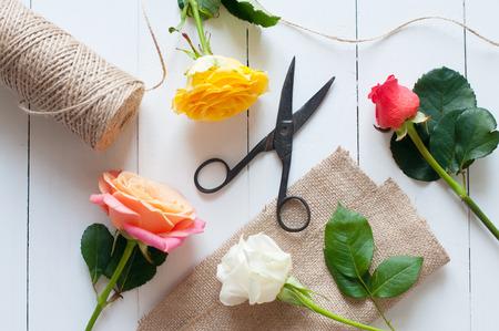 antique scissors: Disposizione floreale, vintage background floristica, rose colorate, forbici antichi e una corda su bianco tavolo in legno verniciato Archivio Fotografico