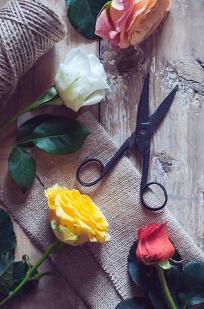 antique scissors: Vintage sfondo floristico, rose colorate, forbici antichi e una corda su un vecchio tavolo di legno