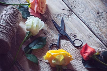 antique scissors: Vintage sfondo floristico, rose colorate, forbici d'epoca e una corda su un vecchio tavolo di legno