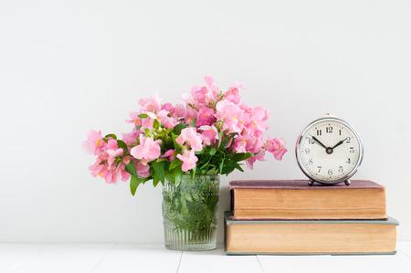 Retro home decor: een stapel boeken, bloemen en een vintage wekker op een witte muur plank