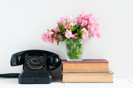 Retro home decor: a stack of books, rotary phone, flowers and a vintage alarm clock on a white wall shelf