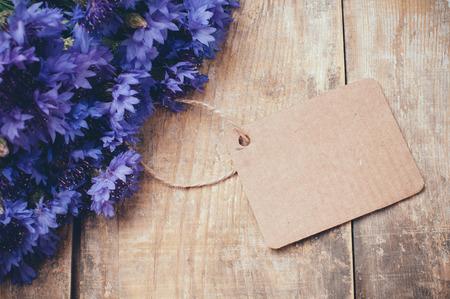 bluet: Rustic bouquet of blue cornflowers and brown cardboard tag on vintage wooden board Stock Photo