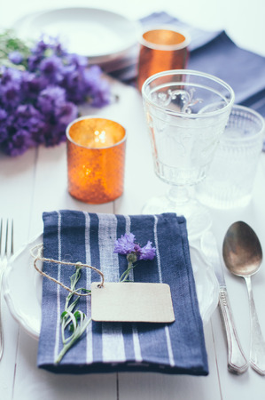 Vintage home table setting with blue napkins, antique cutlery and purple cornflowers on white wooden table. Blank cardboard tag and an old key photo
