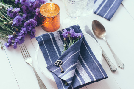 Vintage home table setting with blue napkins, antique cutlery, old key and purple cornflowers on white wooden table. photo