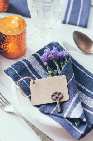bluet: Vintage home table setting with blue napkins, antique cutlery and purple cornflowers on white wooden table. Blank cardboard tag and an old key