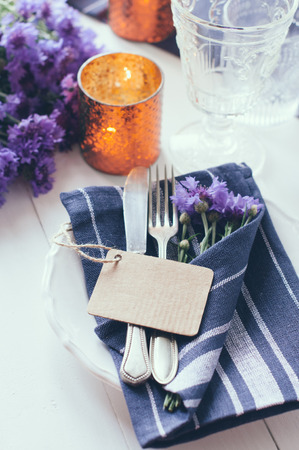 bluet: Vintage home table setting with blue napkins, antique cutlery and purple cornflowers on white wooden table. Blank cardboard tag. Stock Photo