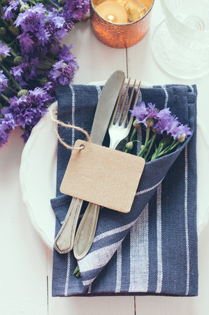 Vintage home table setting with blue napkins, antique cutlery and purple cornflowers on white wooden table. Blank cardboard tag. photo