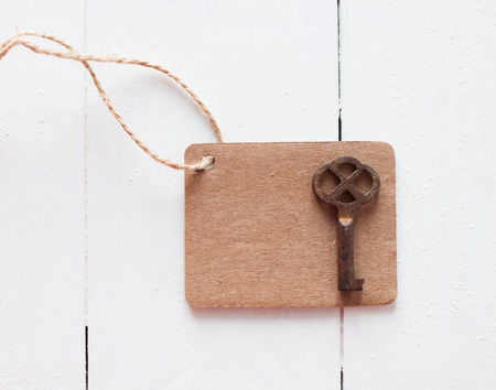 Empty brown cardboard tag on rough rope and rusty antique key on a white wooden board photo