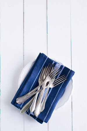 country kitchen: Delicate vintage silverware on blue linen napkin in a plate, antique cutlery om white wooden board, country kitchen background