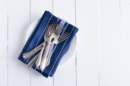 Delicate vintage silverware on blue linen napkin in a plate, antique cutlery om white wooden board, country kitchen background photo