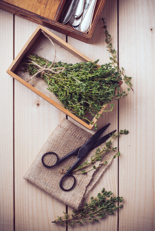 antique scissors: Rustic home kitchen still life, dried herbs, old boxes, antique cutlery and vintage scissors on a wooden table.
