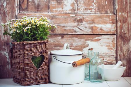 Flores en una cesta de mimbre, botellas de vidrio y lata de leche de la vendimia sobre fondo de madera, casa acogedora decoración rústica, casa habitable