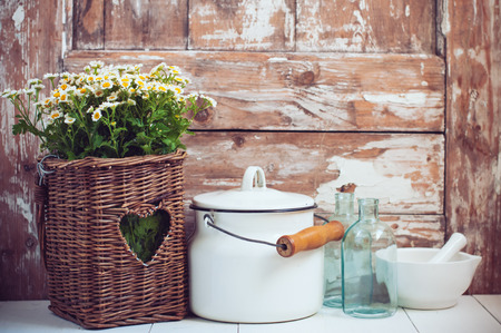 shelf: Flowers in a wicker basket, glass bottles and vintage milk can on wooden background, cozy home rustic decor, cottage living Stock Photo