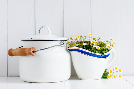 country kitchen: Chamomile flowers in vintage ceramic gravy boat and enamel milk can on white wooden background, home rustic decor Stock Photo