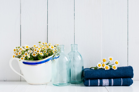 Chamomile flowers in vintage ceramic gravy boat, glass bottles and navy linen towels on white wooden background, home kitchen rustic decor photo