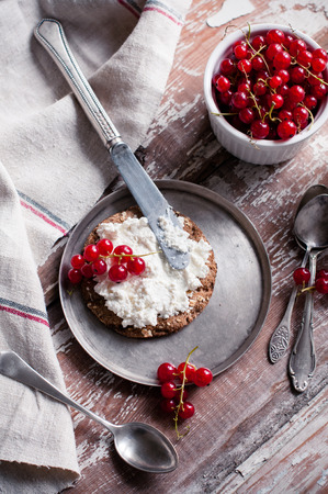 Natural healthy food, grain bread, cheese and fresh organic red currants on an old wooden kitchen table with linen cloth and vintage cutlery. Seasonal berries, rustic breakfast. photo