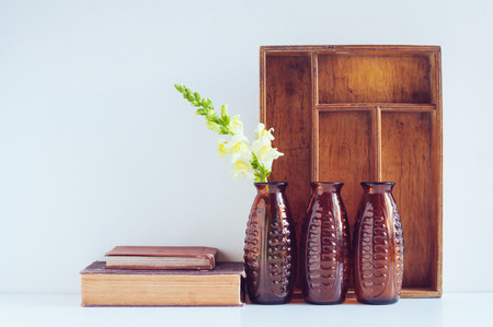 living thing: Vintage home decor, three brown glass flower vases, wooden box and old books on a white background.